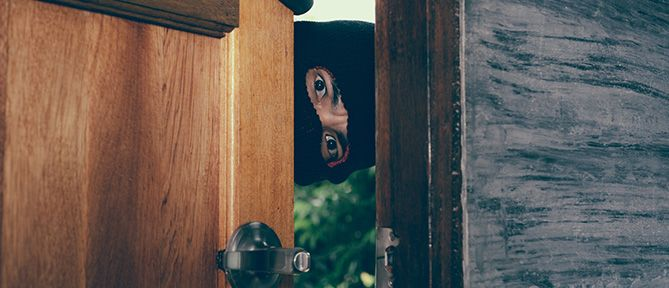 man in mask peeping through door