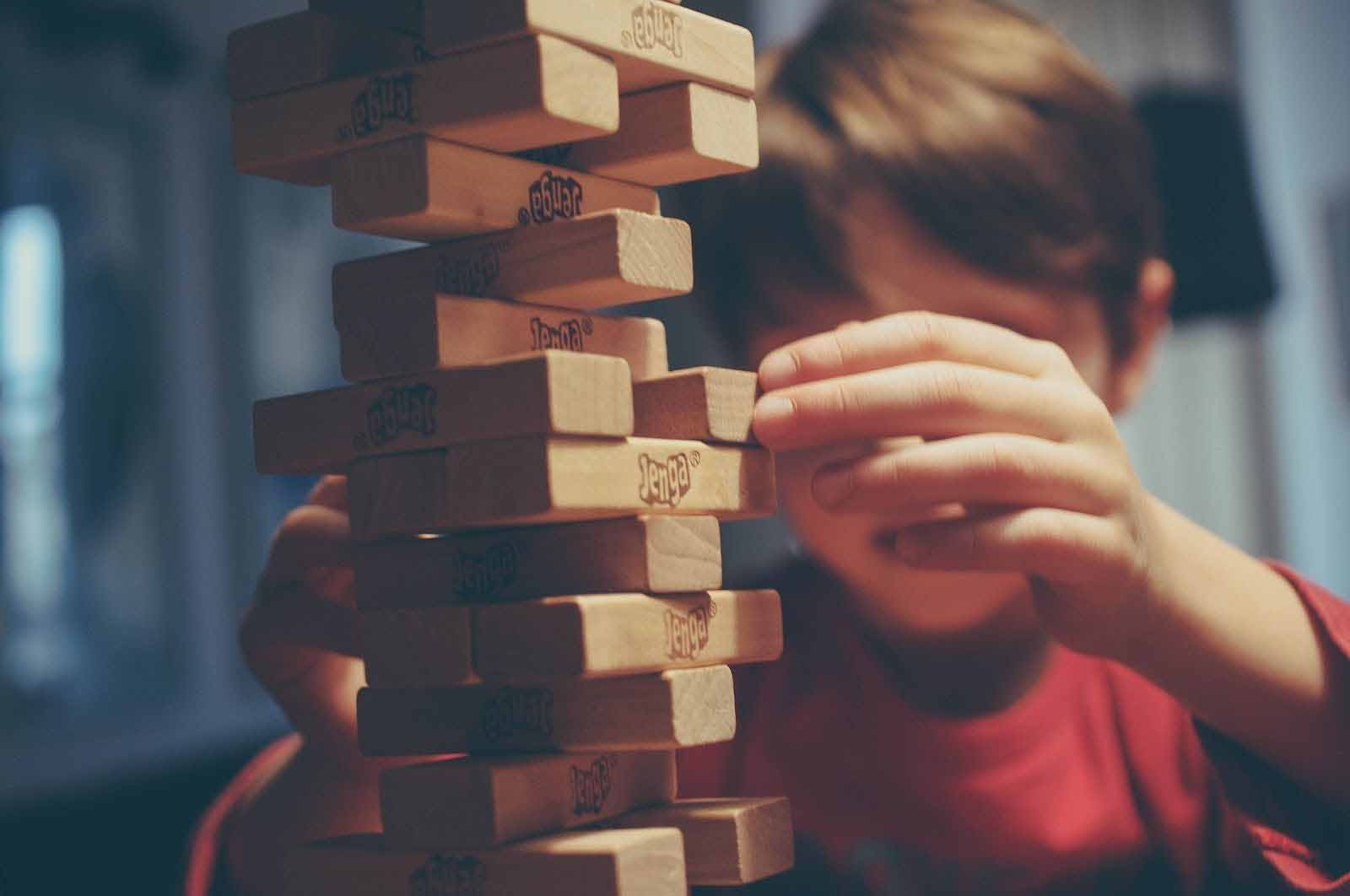 little boy playing wooden building block brick game